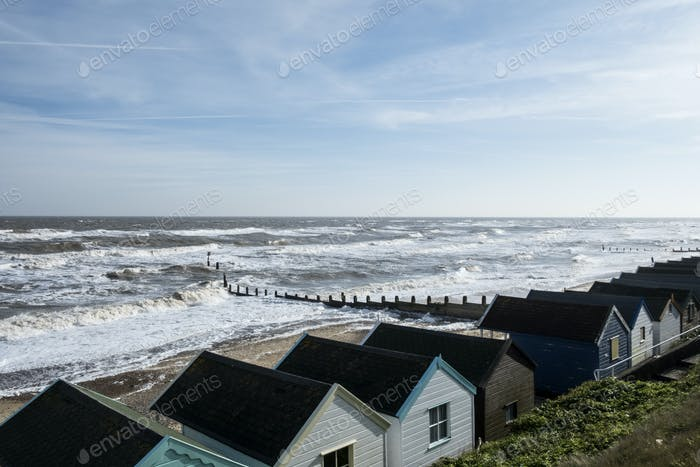 Seascape over a row of wooden beach huts, with waves rolling onto beach near groyne.