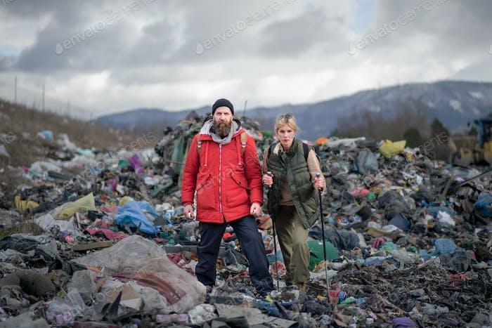 Hombres y mujeres excursionistas en vertederos, concepto ambiental