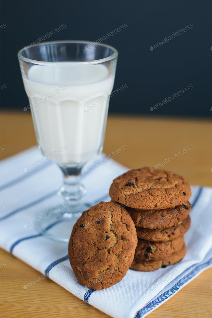 cookies stack with raisins and milk on napkin on table