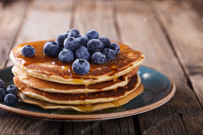 Pfannkuchen gefaltet Stapel mit flüssigem Honig und frischen Heidelbeeren