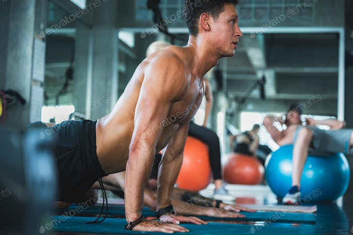 Adult sport man do yoga and pilates for strong and wellness body muscle at gym. Bodybuilder concept.
