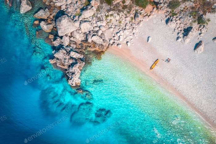 Aerial view of sandy beach with couple and canoe and blue sea