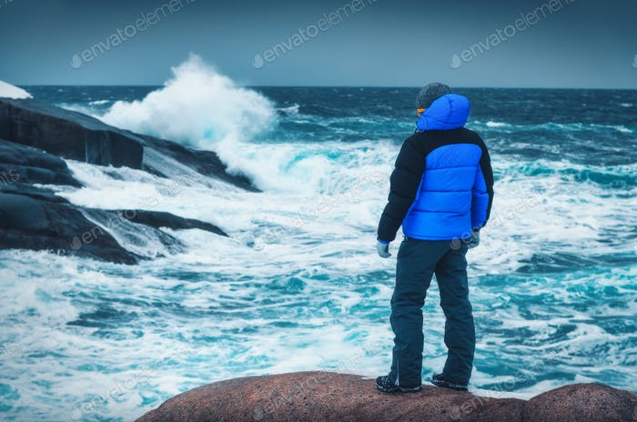 Man in blue jacket is standing on the stone on sea coast