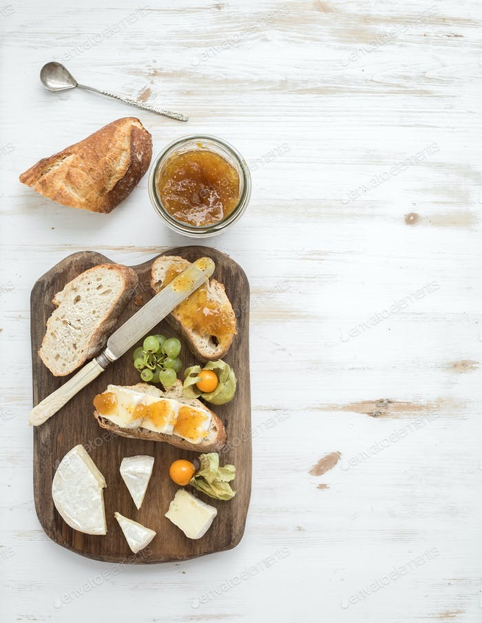 Breakfast set. Brie cheese and fig jam sandwiches with fresh grapes, ground cherries. Top view