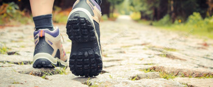 Legs of woman in hiking boots on tourist trail in mountain