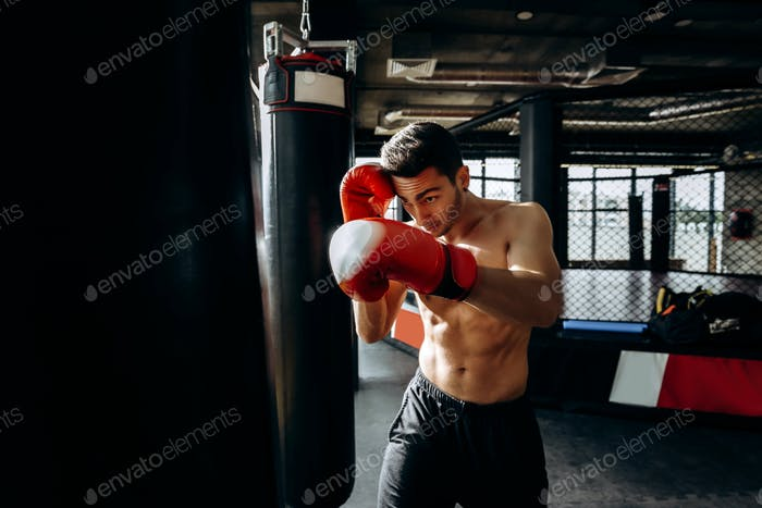 Sportsman in red boxing gloves with a naked torso hits punching bag in the gym on the background of