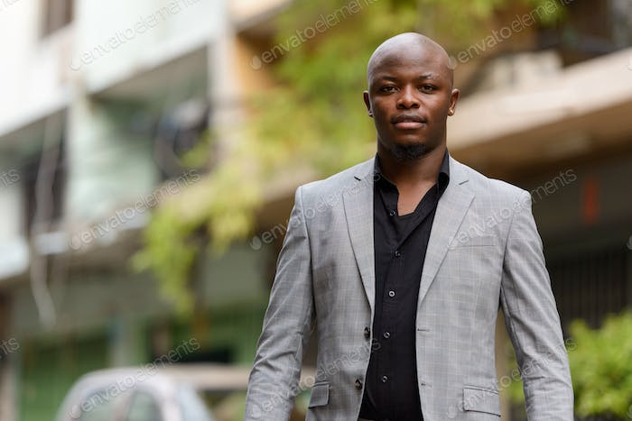 Happy young handsome bald African businessman smiling outdoors