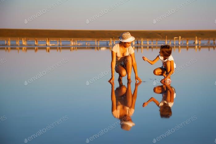 Две фантастически красивые девушки на красивом прозрачном озере ищут что-то в