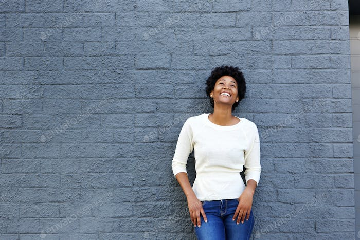 Cheerful young black woman standing against gray wall