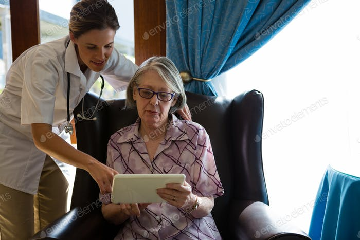 Female doctor assisting woman in using tablet at retirement home