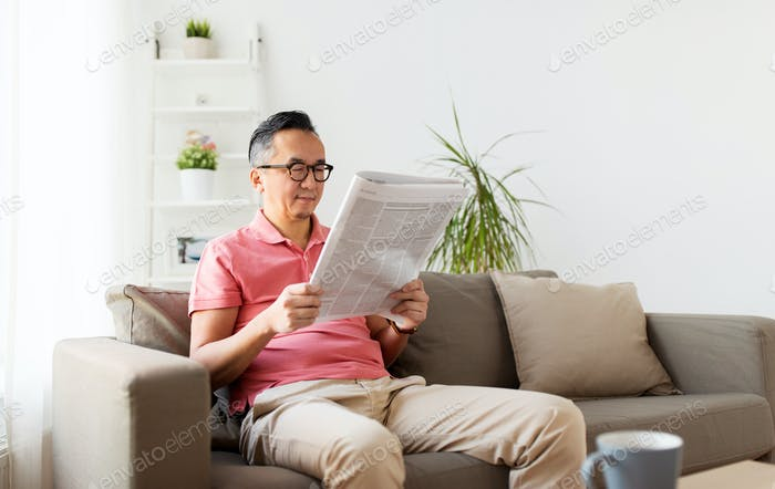 asian man in glasses reading newspaper at home