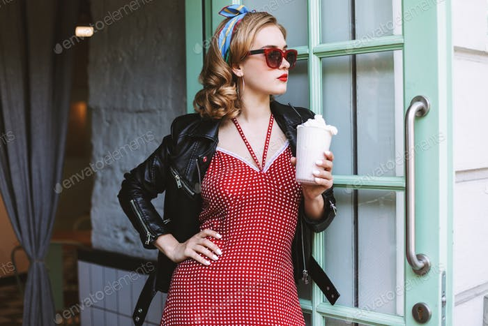 Beautiful girl in sunglasses standing in doorway at cafe with milkshake thoughtfully looking aside