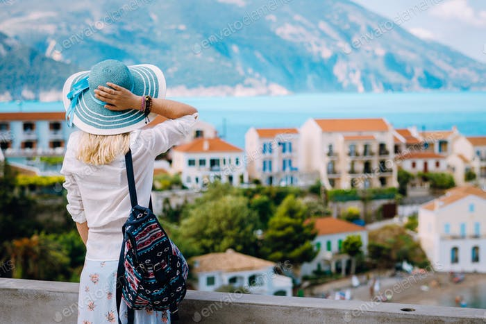 Tourist woman admiring view of colorful tranquil village Assos on morning. Young stylish female