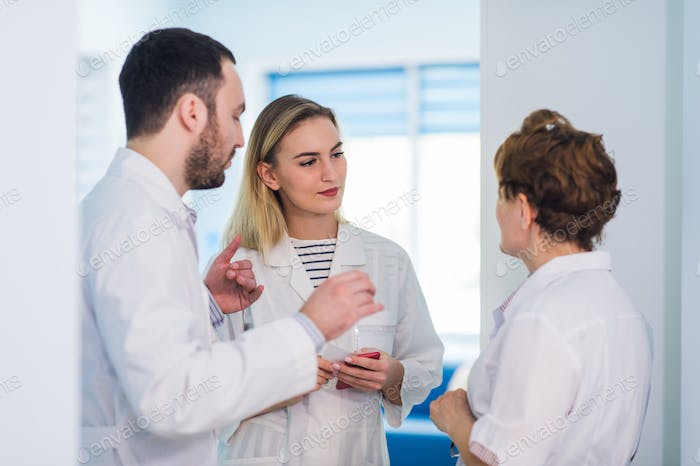 Mature doctor discussing with nurses in a hallway hospital.