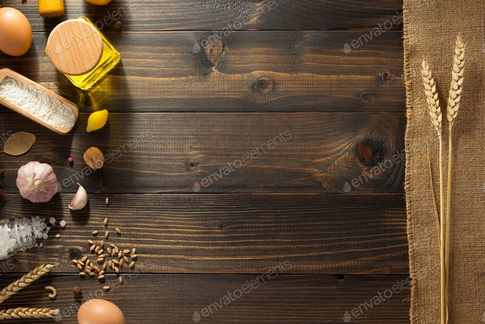 ears of wheat and bakery ingredients on wood