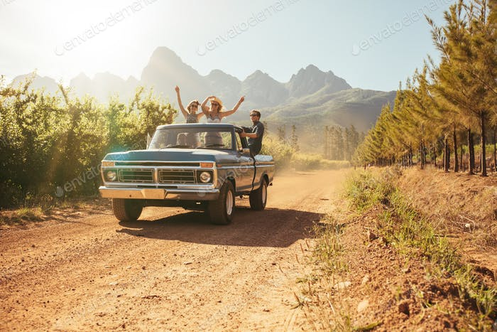 Friends in the open back of a vintage truck on a summer day