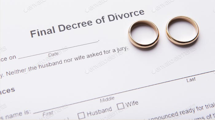 Two golden wedding rings on final divorce decree document
