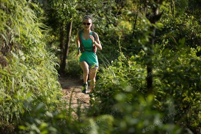 Female trail runner running in sunny forest