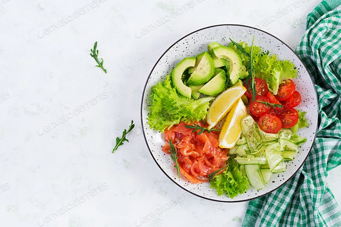 Salad of salted fish salmon, avocado, cherry tomatoes, cucumber, lettuce and lemon.