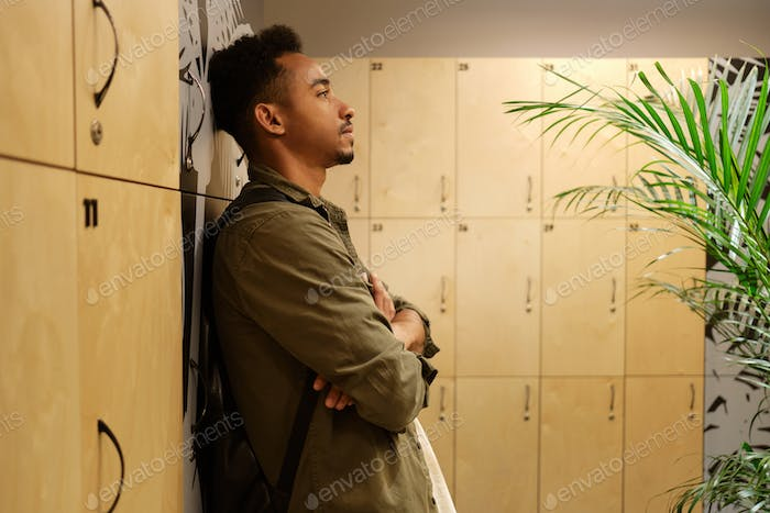 Young handsome casual African American man thoughtfully standing in locker room