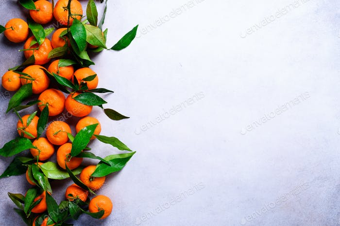 Orange tangerines (oranges, mandarins, clementines, citrus fruits) with green leaves on light