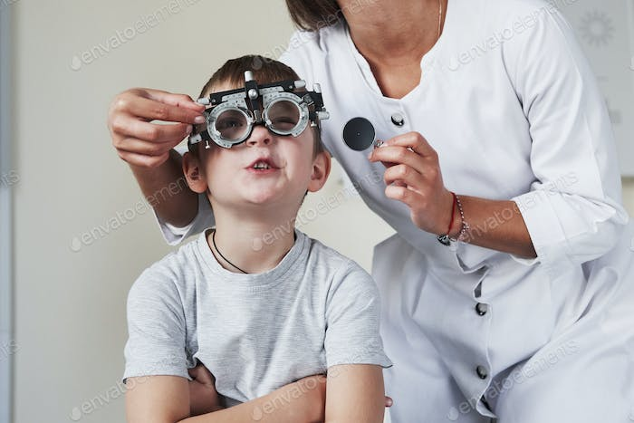 Hardly concentrating. Doctor tuning the phoropter to to determine visual acuity of the little boy