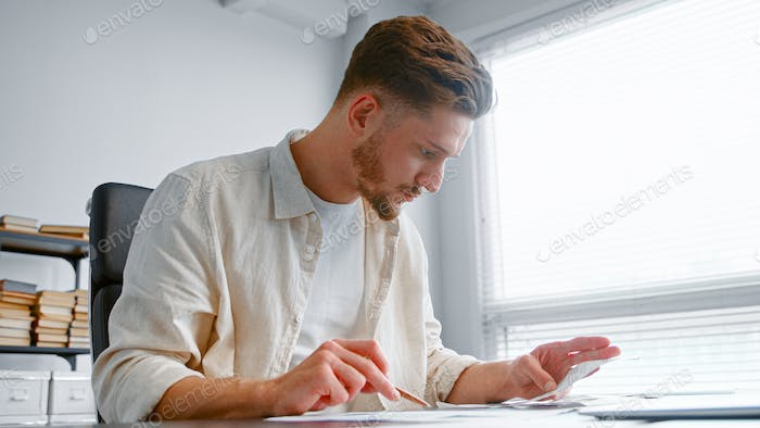 Bearded guy experienced accountant summarizes income comparing invoice receipts