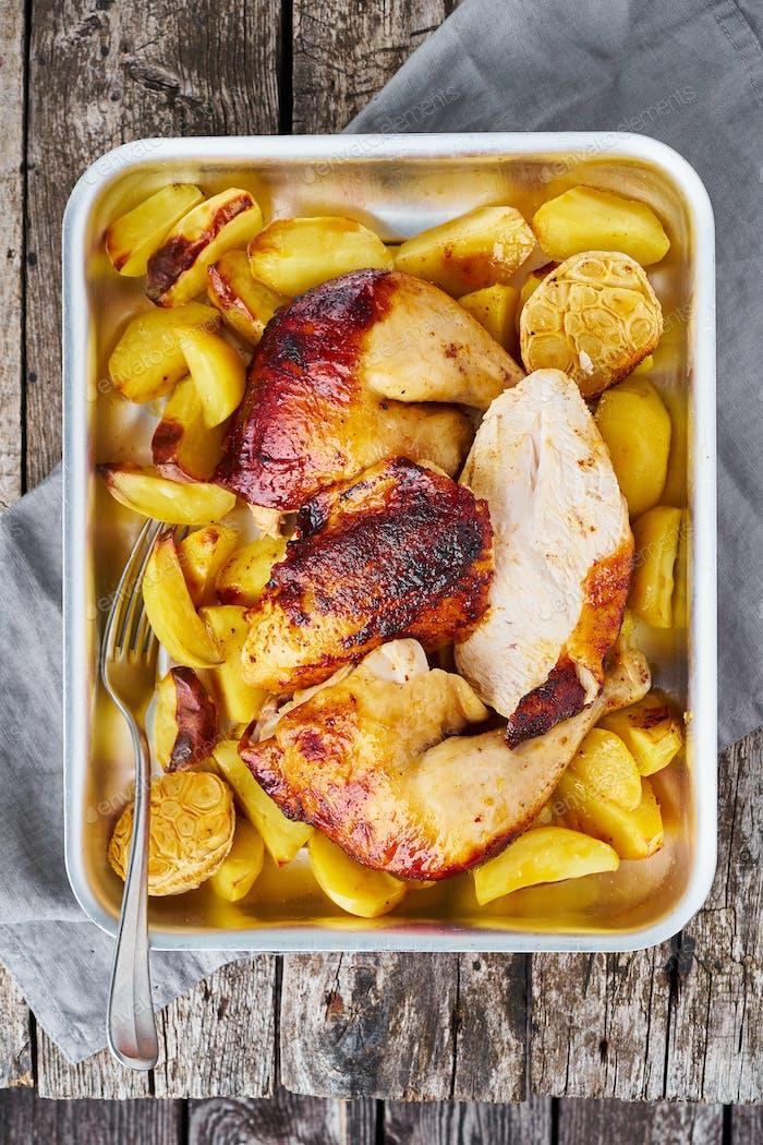 Gegrilltes Huhn in blauem Auflauf auf dunkelgrau alten Holztisch,