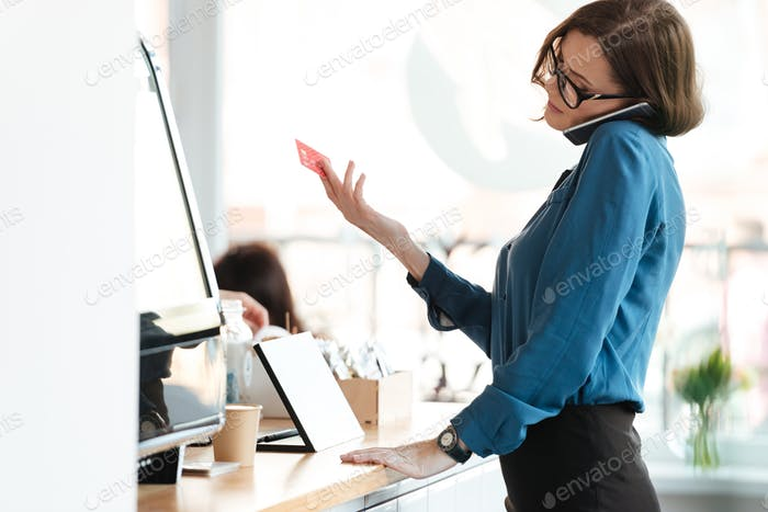 Woman standing in cafe holding credit card talking by phone