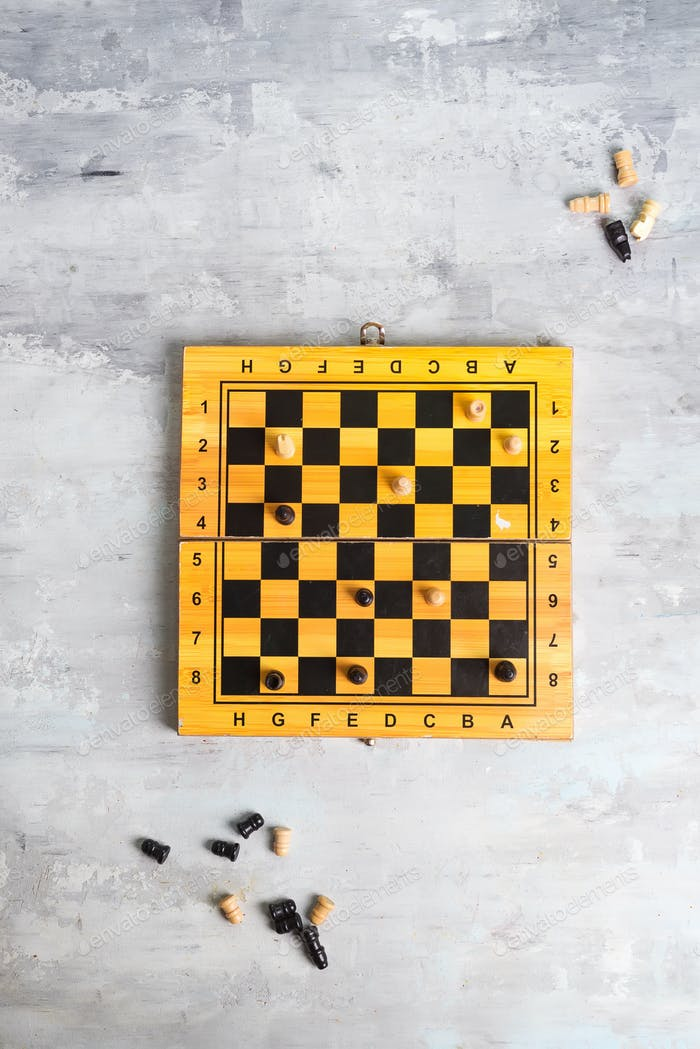 wooden chess board and making chess move on stone background, flat lay
