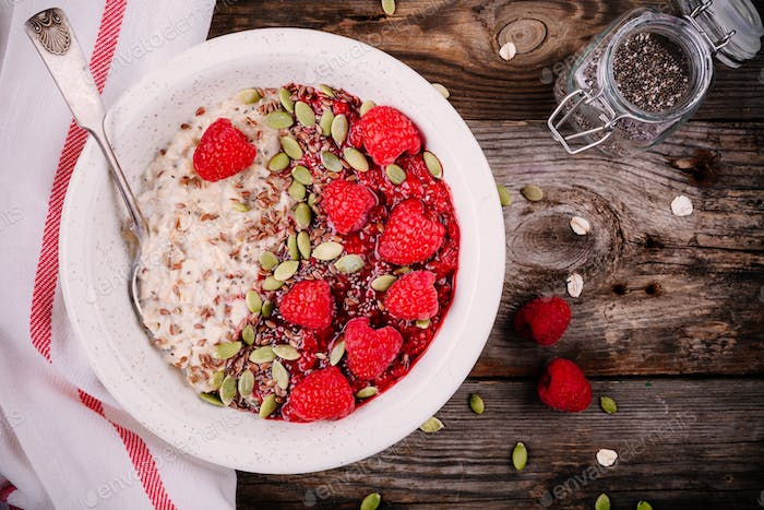 Healthy breakfast: porridge with fresh raspberries, flax seeds and pumpkin seeds