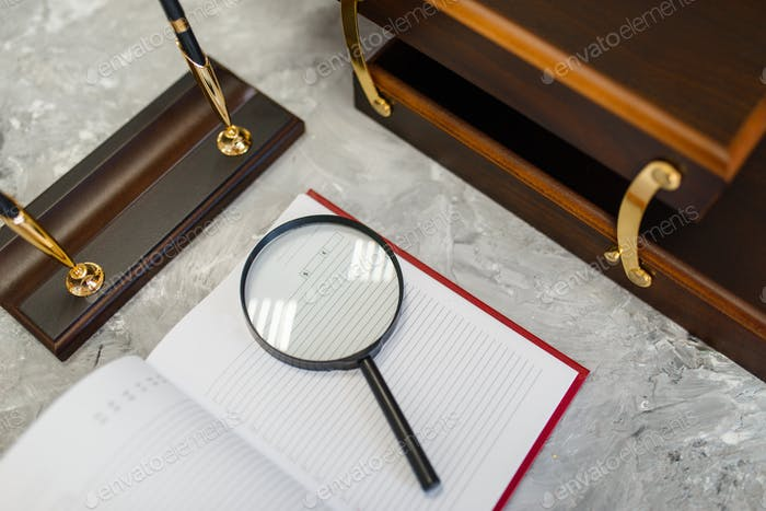 Notebook and magnifier on table, stationery store