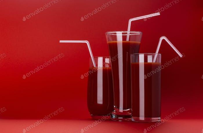 Glas Tomatensaft isoliert auf rotem Hintergrund mit Kopierraum