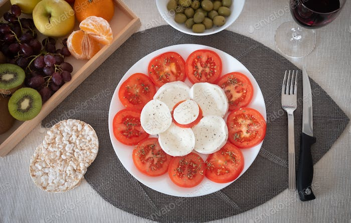 Stay fit with a light and healthy dish of tomato and mozzarella. Accompanied by rice cakes and fruit