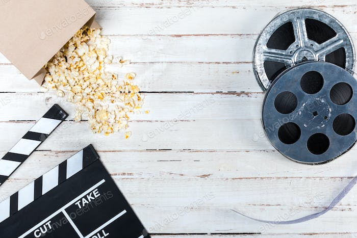 Top view of film reels, popcorn and movie clapper on wooden table, Movie time concept