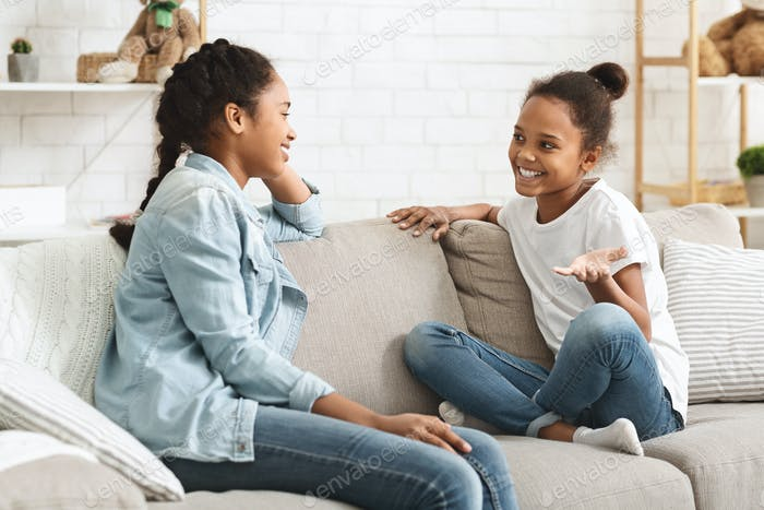 Two lovely black sisters having conversation at home