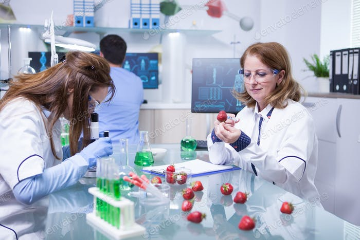 Middle age female in white coat working as scientist in a lab research