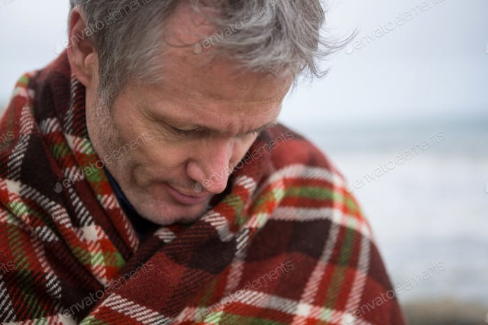 Man wrapped in shawl looking down