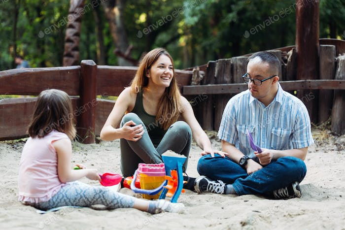 Happy family spending fun time together playing in sand