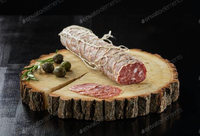 Salami sausage and olives over black