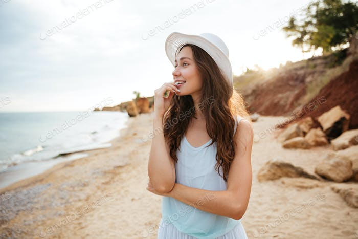 Cheerful young woman walking on the beach