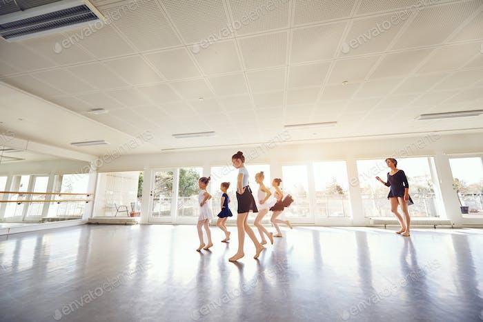 Teacher watching little ballerinas performing dance in class