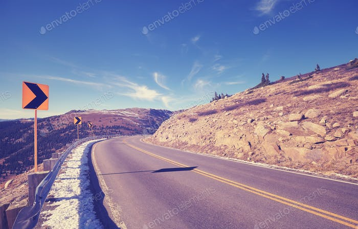 Vintage toned mountain asphalt road turn, travel warning concept