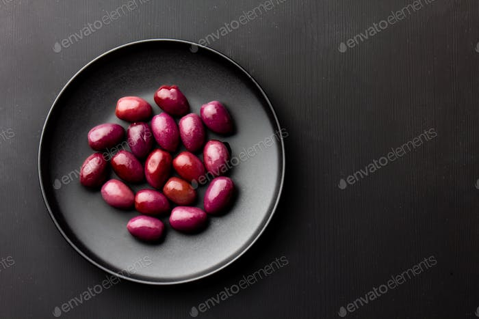 Purple olives on black plate, copy space