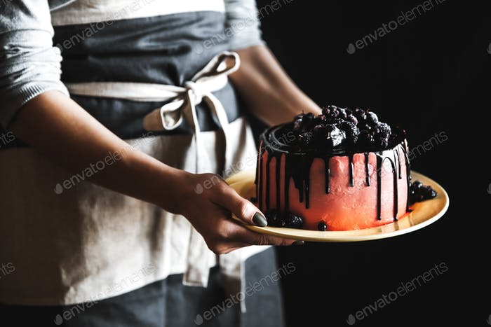 Woman Chef in black apron holds cake decorated with berries and fruits with two hands