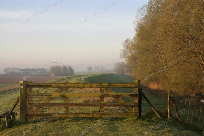 Geschlossenes Tor auf einem Deich an einem nebligen Morgen in der Nähe des niederländischen Dorfes Werkendam