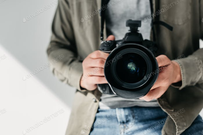 cropped view of professional male photographer with digital photo camera in photo studio