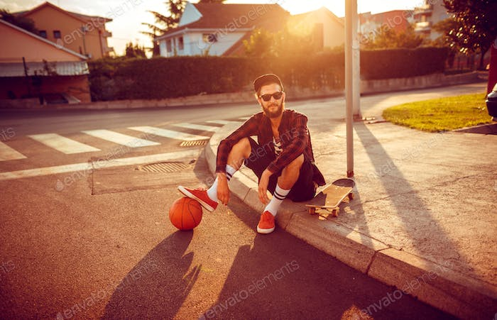 Young stylish man with a basketball and skateboard sitting on a