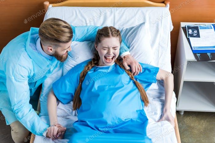 schwangere Frau bei der Geburt im Krankenhaus, während der Mann sie umarmt