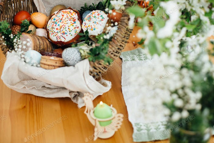 Easter modern eggs, cake, ham, beets, butter in rustic basket decorated with green buxus branches